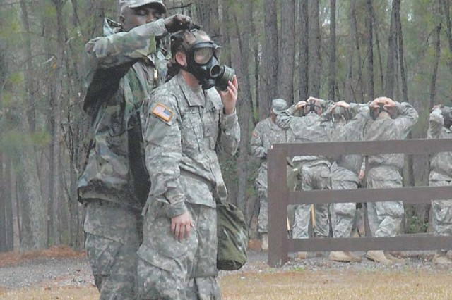 Sgt. 1st Class Morris Starling, range instructor, helps Pvt. Jennifer Christensen, Company A, 2nd Battalion, 60th Infantry Regiment, adjust her protective mask before entering the NBC chamber.