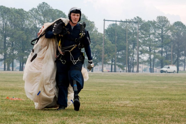 Spc. Max Ramsey, who lost his left leg in Iraq in March 2006, carries his parachute after a practice jump as member of the Screaming Eagles Parachute Demonstration Team at Fort Campbell, Ky., March 13.
