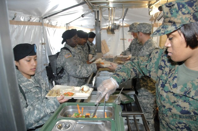 Marine Sgt. Calle Bennet and the Pentagon Team feed Soldiers as part of the field competition.