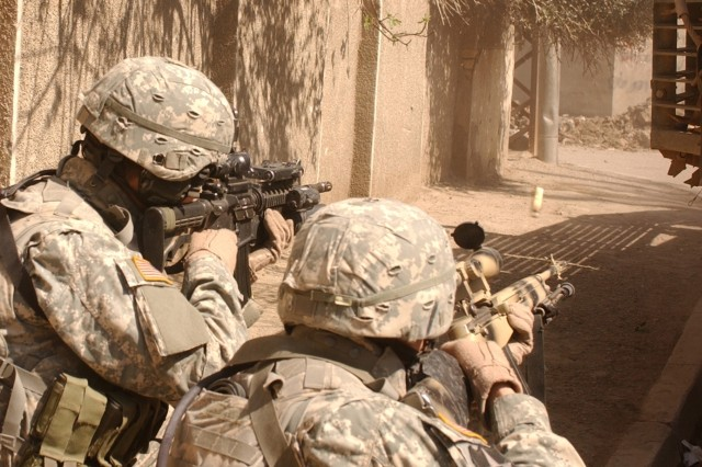 Sgt. Karl King and Pfc. David Valenzuela lay down cover fire while their squad maneuvers down a street from behind the cover of a Stryker combat vehicle to engage gunmen who fired on their convoy in Al Doura, Iraq, March 7.  The Soldiers are from Company C, 5th Battalion, 20th Infantry Regiment, 3rd Brigade Combat Team, 2nd Infantry Division.