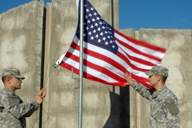 Spc. Michael Tyree of the 73rd Cavalry Regiment's 1st Squadron lowers an American Flag flying over his unit's headquarters in Northern Iraq. Spc. Fabian Acosta catches the flag as it lowers.