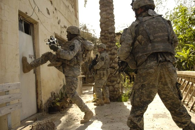 Soldiers break down a door to engage the anti-Iraqi forces inside.