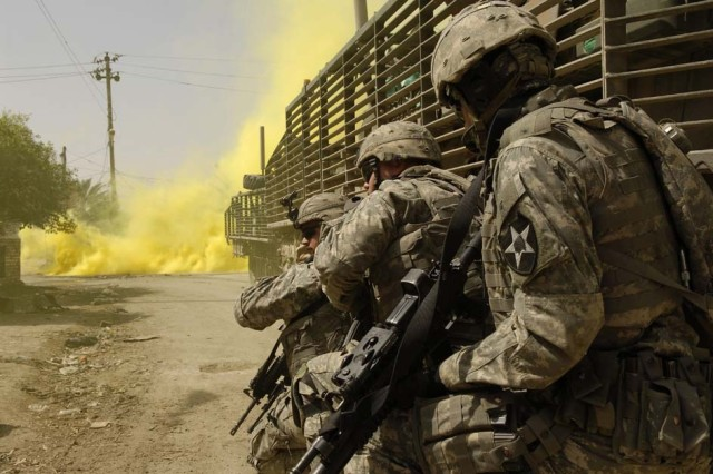 Other Soldiers utilize their Stryker vehicle for cover as they engage anti-Iraqi forces.