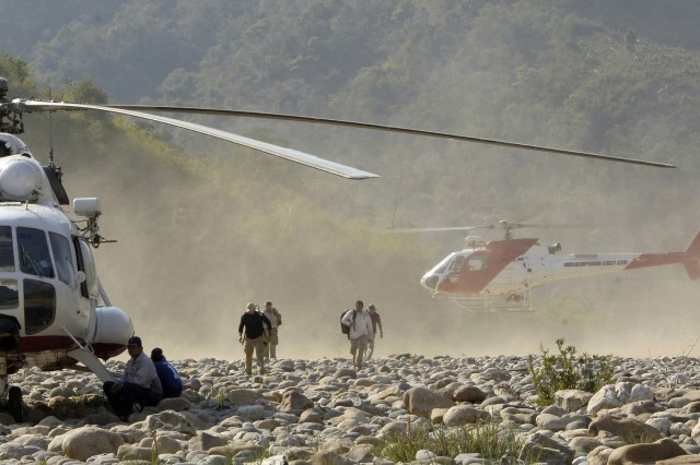 The team arrives at a remote site by helicopter.