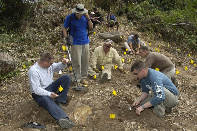 The team searches a site on the side of a mountain, marking the locations where gear and remains are discovered.