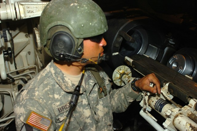 Spc. Eduardo Briseno, a cannoneer who loads and fires howitzers for the 82nd Field Artillery Regiment's Alpha Battery, 1st Battalion, prepares to load a charge into the barrel of a howitzer on an M109A6 Paladin, March 13 on Camp Taji, Iraq, during the first-ever calibration firing of the Modular Artillery Charge System in the combat zone by an entire Paladin battery.