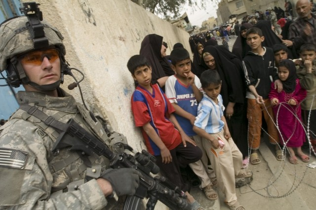 Staff Sgt. Buddy Tucker, a paratrooper with Headquarters Company, 2nd Battalion, 325th Airborne Infantry Regiment, 2nd Brigade Combat Team, 82nd Airborne Division, guards the entrance to a schoolhouse converted into a medical clinic for a joint U.S.-Iraqi medical operation in Baghdad