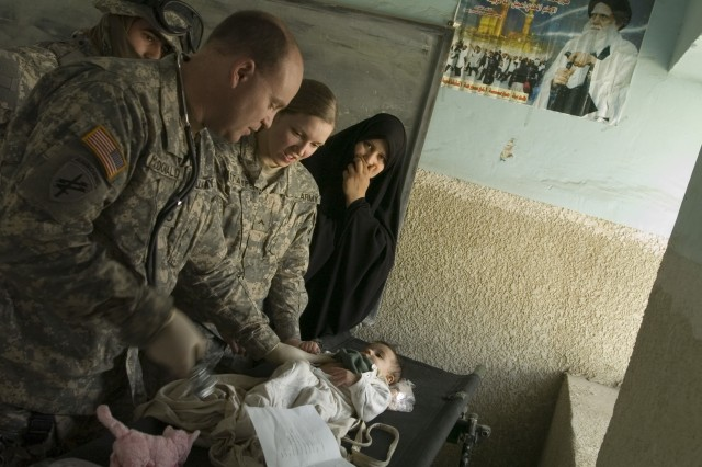 Staff Sgt. Steven McDonald, a civil affairs medic with Headquarters Company, 2nd Brigade Combat Team, 82nd Airborne Division, and Pvt. April Stamper, a medic with Company C, 407th Brigade Support Battalion, 2nd Brigade Combat Team, 82nd Airborne Division, treat an Iraqi woman's sick baby during a joint U.S.-Iraqi medical operation in Baghdad's Sadr City neighborhood March 17.