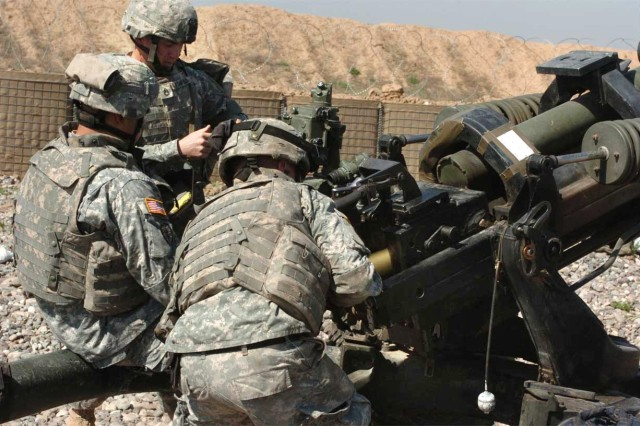 Staff Sgt. Clinton Stanfield, a section crew chief and Spc. Christopher Flores, a gunner, verify coordinates while Pfc. Chealse McMillian, an assistant gunner, loads a round.