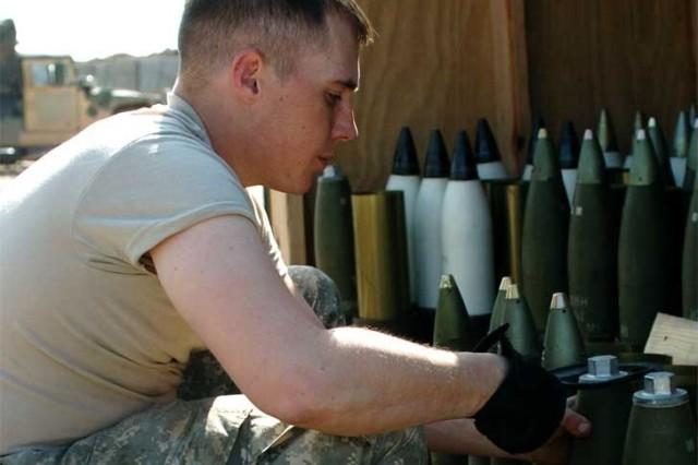 Pfc. Chealse McMillian, an assistant gunner, prepares the ammunition.