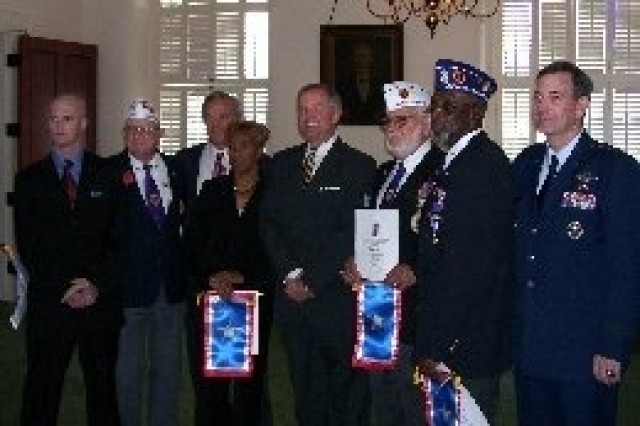 """Following Alabama Gov. Bob Riley's official declaration that his state will recognize May 1 as """"Silver Star Day,"""" state Rep. Greg Wren (fifth from left) held a reception for four veterans wounded in four different conflicts. Sean Phillips (from left), a veteran of the Iraq war; David Cox, a World War II veteran; Speaker Seth Hammett; Deloris Bryson, Leroy Arceneaux, a Korean War veteran; Robert Jones, a Vietnam veteran; and Air Force Lt. General Stephen Lorenz attended. Each veteran was presented a Silver Star Families of America banner in recognition of their sacrifices. Bryson, a Gold Star Mother, attended in honor of her son, Marine Gunnery Sgt. Stephen Bryson, who was killed in action."""