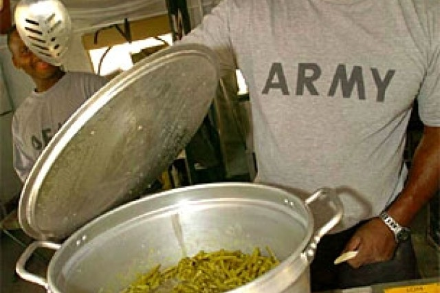 """Sgt. James Williams, of Natchitoches, La., checks on some green beans just before the dinner meal inside the """"containerized kitchen"""" at Forward Operating Base Hope in Baghdad, March 14."""