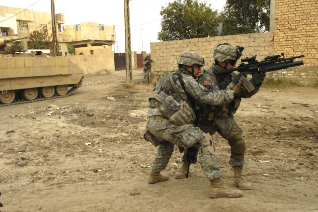 Spc. William McGrath gets a spare magazine from Spc. Cory Barton during the firefight. Soldiers help each other out like this all the time when the going gets tough.