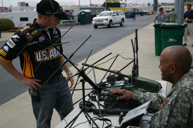 Army driver, Regan Smith, discusses Special Forces communications equipment with Sgt. 1st Class Keith Megginson, 7th Special Forces Group (Airborne), at a special demonstration on the infield of the Atlanta Motor Speedway.