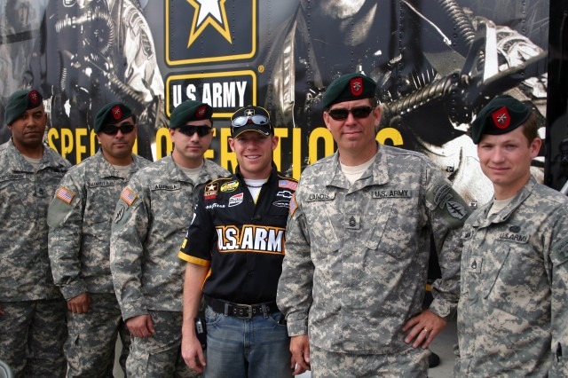 """Members of ODA 783, B Company, 3rd Battalion, 7th Special Forces Group (Airborne) pause for a photograph with Army """"01"""" car driver, Regan Smith. The team members are providing a Special Forces equipment demonstration at the Atlanta Motor Speedway. Pictured (l. to r.) are Sgt. 1st Class Keith Megginson, Staff Sergeants Carlos Chumpataz and Anthony Aguiniga, Smith, Master Sgt. Todd Landis, and Staff Sgt. Wiley MacCormack."""
