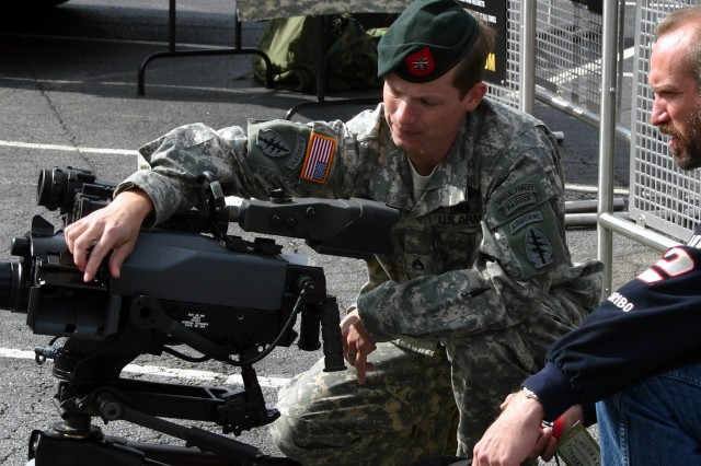 Staff Sgt. Wiley MacCormack, 7th Special Forces Group (Airborne), explains a crew-served M47 40mm gun to a race fan outside the Atlanta Motor Speedway.