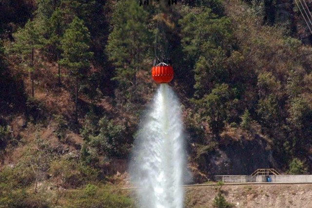 The Soldiers release the water from the bucket using a remote control device. In a real situation, the water would be released over a structural blaze or wildfire.