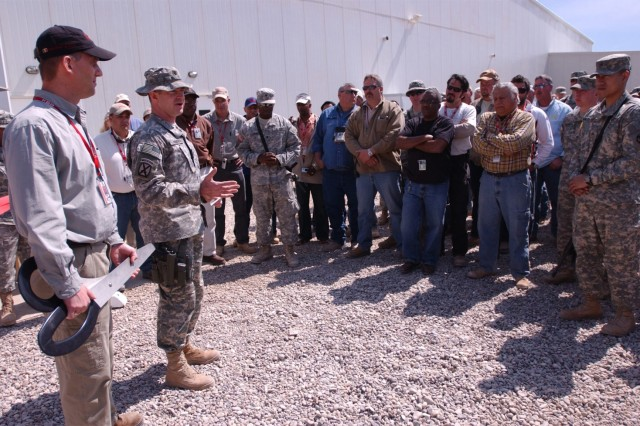 Lt. Col. Frank Andrews, a native of Apex, N.C., and the executive officer for the 2nd Brigade Combat Team, 10th Mountain Division thanks the civilians and Soldiers who have helped get the new Camp Striker, Iraq, dining facility on its legs during the facility's grand opening March 20. Christian LeMoine, a native of Antwerp, Belgium, and the dining facility manager, a civilian contractor with Kellogg, Brown and Root, stands by with oversized scissors to cut the ceremonial ribbon.