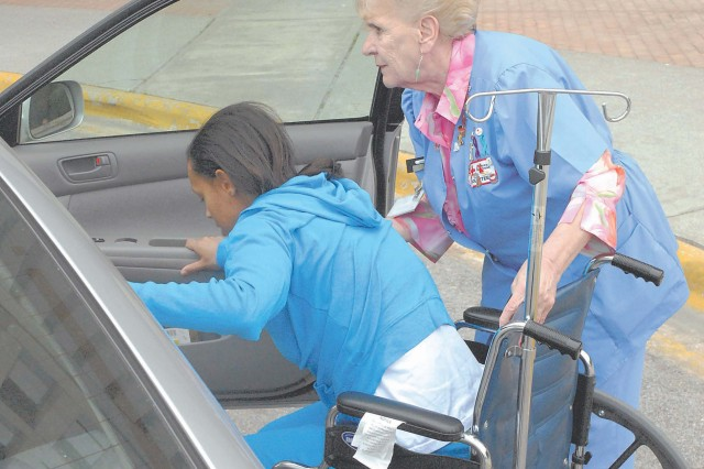 Red Cross volunteer Edith Currie helps a patient at Moncrief Army Community Hospital into a vehicle. Currie helps transport patients throughout the hospital. She is one of four volunteers being honored as a Hometown Hero by the Red Cross this month for their service.