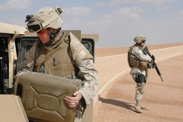 Gunnery Sgt. Scott Stalker refuels the vehicle during a tactical stop en route to Ar'Ar, Iraq. Marine Capt. Daniel Sanchez provides security, along with Army Sgt. Alexander (inside the vehicle in previous photo).