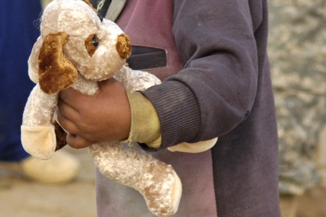 An Iraqi child holds a stuffed animal that was given to him by U.S. Soldiers prior to the opening of the water project. He and others are benefiting from the project.