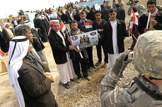 Iraqi residents pose for a photo during the opening of the water treatment plant.