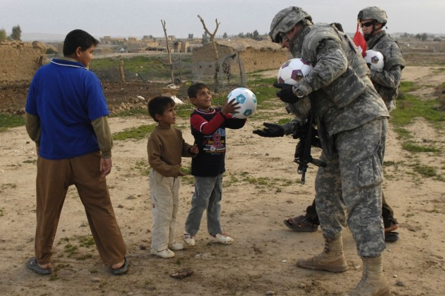 Soldiers pass out soccer balls to Iraqi children prior to the opening of the water project.