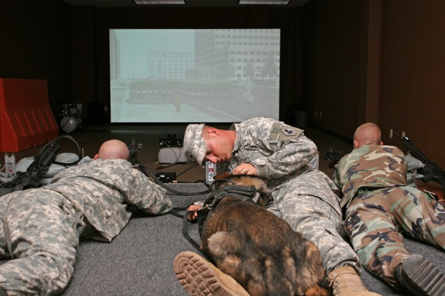 Sgt. James Adolfson, 18th Military Police Detachment, Canine Section, comforts military police dog J.R. who is taking part in noise training in the Engagement Skills 2000 trainer here. The training helps desensitize MP dogs to the loud noises of battle and prepares them for deployment.