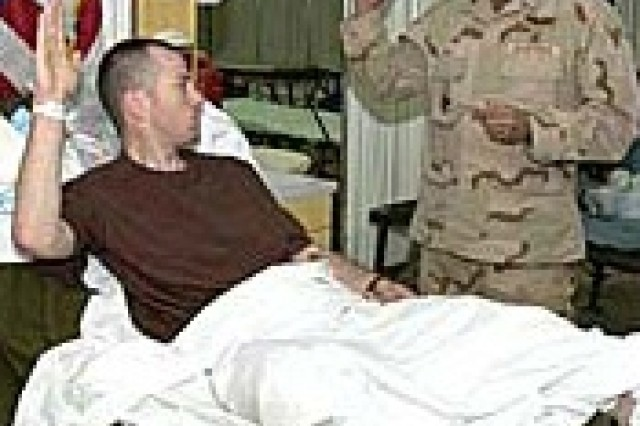 Staff Sgt. Andrew S. McMann, a squad leader, while reenlisting in a medical facility in Iraq, March 25, just 48 hours after being wounded by an IED in Ramadi.