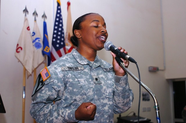 """Spc. Kimberly Taylor, a vocalist for the 1st Cavalry Division Band, sings """"I am a Believer"""" during the Women\'s History Month celebration hosted by 615th Aviation Support Battalion, 1st Air Cavalry Brigade, 1st Cav. Div., at Camp Taji,"""