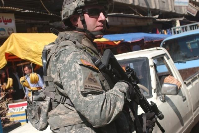 Staff Sgt. William Johnson patrols the Al Noiomanya Al Jammsa neighborhood market.