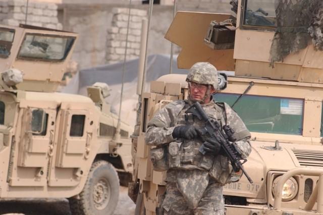 A Soldier patrols the Al Noiomanya Al Jammsa neighborhood market.