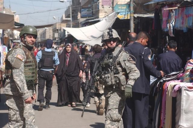 1st Lt. Nicolo Olcese and his interpreter patrol the Al Noiomanya Al Jammsa neighborhood market.