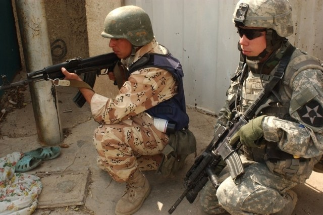 Pfc. Jason Kelly and an Iraqi Soldier work side by side.