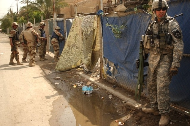 A U.S. Soldier provides security as Iraqi Soldiers enter a courtyard.