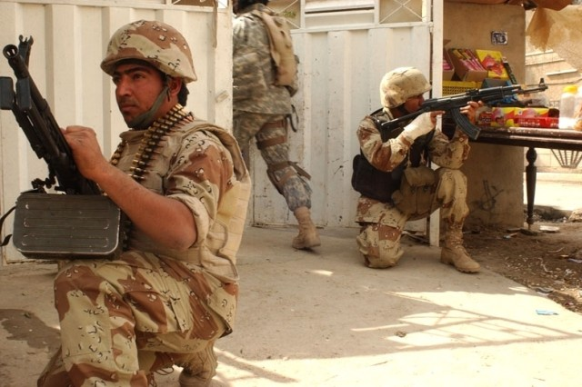 Iraqi Soldiers provide security for fellow Soldiers clearing a house.