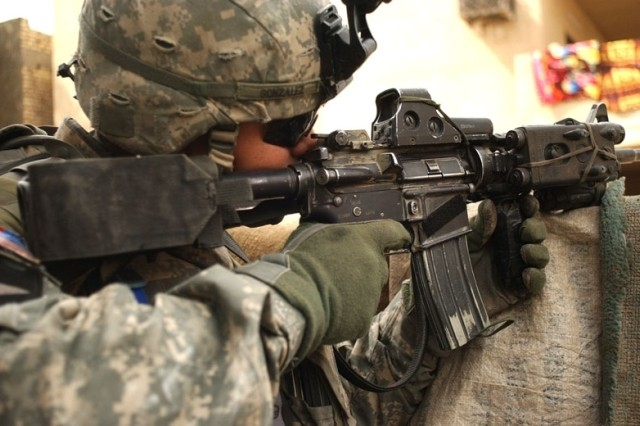 Spc. Ismael Gonzalez uses his scope to check for trouble.