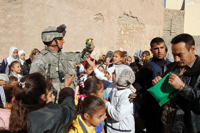 Lt. Col. Malcolm Frost, 3rd Squadron, 4th Cavalry Regiment commander, distributes school supplies to Iraqi children in Tal Afar. Frost said coalition and Iraqi security forces are working to ensure that the recent al Qaeda attack in the city doesn't overshadow the good works done during the past 15 months. Schools and medical clinics have been built and infrastructure and the general economic situation of the residents of Tal Afar have been improved, he said.