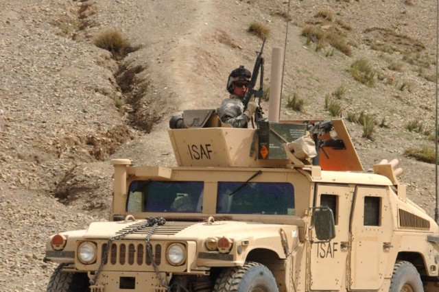 A Soldier from Company C, 1st Battalion, 26th Field Artillery Regiment pulls security in Khowst Province. The Afghan Soldier on the hill is patrolling the area.