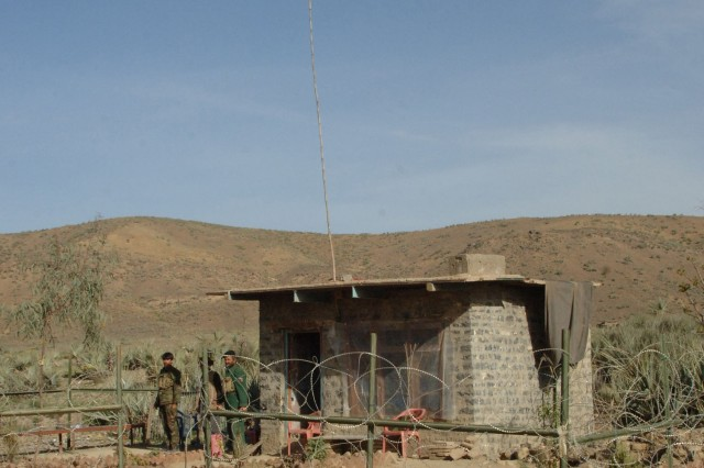 Afghan National Policemen man a guard shack on the road leading across the Pakistan/Afghanistan border below checkpoint 7 in the Tirzaye District of Khowst Province.