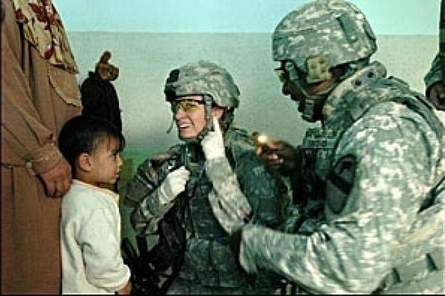 Pfc. Roxanne Nissen, a 1st Cavalry Division, 2nd Brigade Combat Team medic, shows a little patient where the surgeon wants to look during the medical mission in Baghdad, Iraq, March 24.