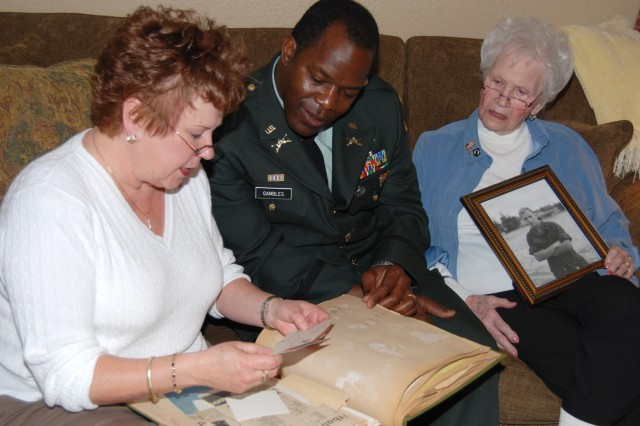 Maj. Kenneth Gambles, assistant product manager at PEO STRI, listens as Mary Lou Wade (left), and Jane R. Wesley (right), bring MIA Soldier Capt. Herbert Crosby to life through stories and photographs. Crosby's UH-1C Huey helicopter went down over Quang Nam Province Jan. 10, 1970. The Vietnam veteran will be laid to rest at Arlington National Cemetary in May.