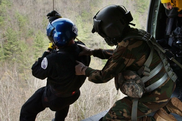 A Soldier assists a member of the North Carolina Helo Aquatic Response Team out of a UH-60 Black Hawk helicopter.