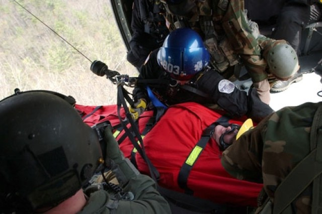 """The """"lost hiker"""" is hoisted aboard the helicopter."""