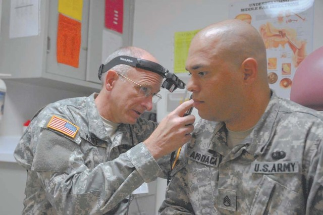 Lt. Col. David McKee, an otolaryngologist at Moncrief Army Community Hospital, examines the ear canal of Staff Sgt. Jeffried Apodaca, Chaplain Center and School. McKee joined the Army Reserve last year at the age of 52.