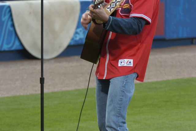 Tracy Byrd, country music artist, sings the National Anthem during the opening day cermony. Byrd gave a pre-game concert to kick off the evening festivities, which included a F-22 Raptor fly-over and a visit from former U.S. President Jimmy Carter.