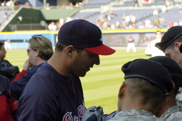 Jeff Francoeur, an outfielder with the Atlanta Braves, takes time out during pre-game practice to sign autographs for the Soldiers.