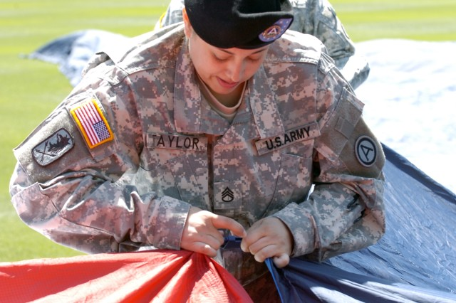 Staff Sgt. Rosalina Taylor, a automated logistical sergeant with Headquarters and Headquarters Company, Third Army/U.S. Army Central assembles the flag before the Atlanta Braves opening day ceremony April 6 at Turner Field in Atlanta.