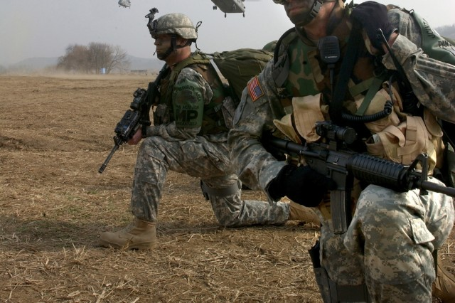 Command Sgt. Maj. Daniel Ciarrochi and Sgt. 1st Class James Breakfield secure a helicopter landing zone for a Republic of Korea Army Chinook  helicopter.