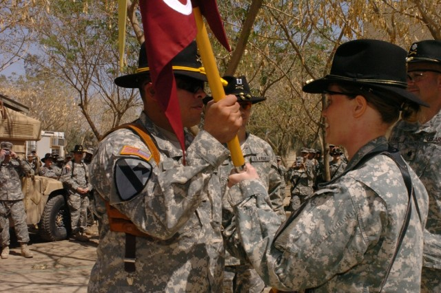 Capt. Teresa Murray, of West Palm Beach, Fla., passes the unit colors to 1st Sgt. Anthony Pena during the Company C, 15th Brigade Support Battalion's change of command ceremony on Forward Operating Base Prosperity, Iraq April 1.